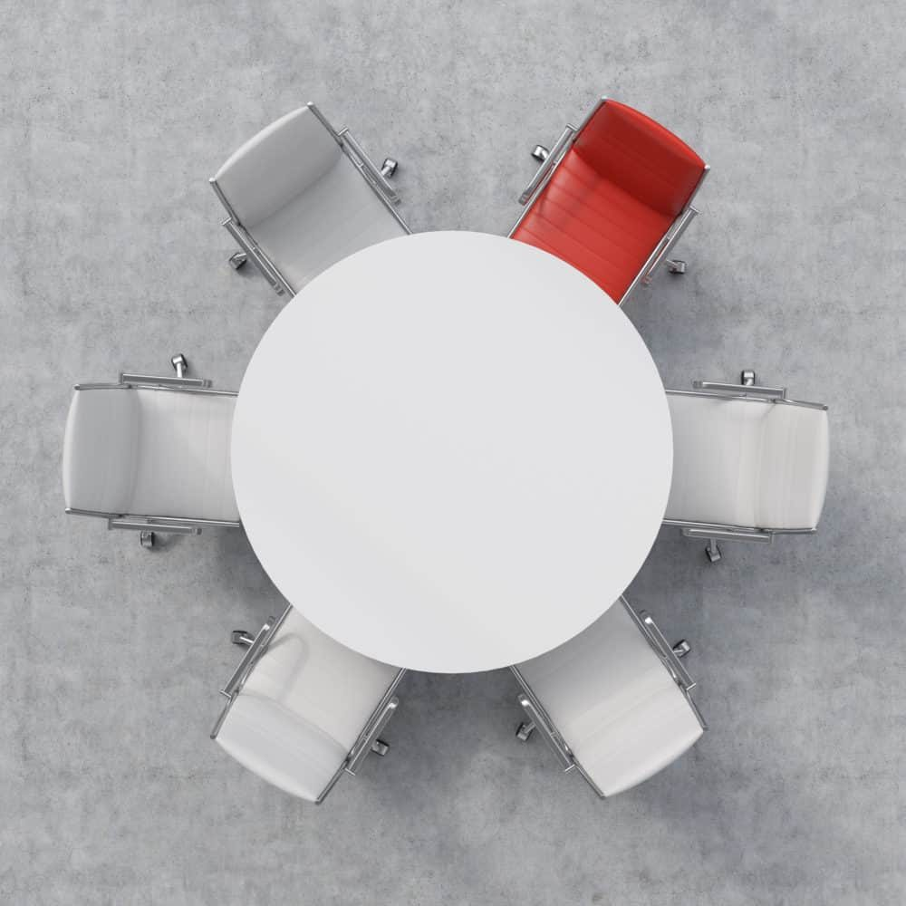 Top view of a conference room. A white Roundtable and one red and five white chairs.